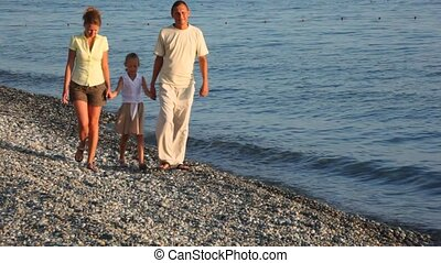 walking happy family with girl on pebble beach, to camera