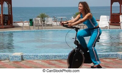 happy young woman training on exercise bicycle, pool and sea in background