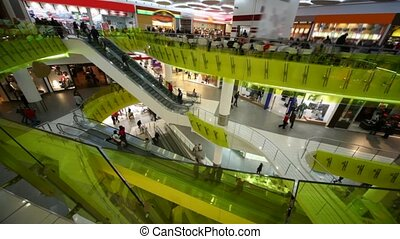 people rushing on escalators in multistorey mall
