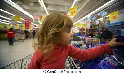 little girl sitting in shopping trolley buying toys in mall