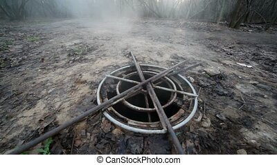 steaming sewer manhole in forest