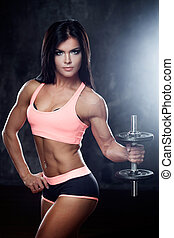Muscular female body. Young strong athlete posing on dark textured background