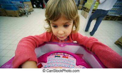 little girl playing logic game in mall, rejoices to victory...