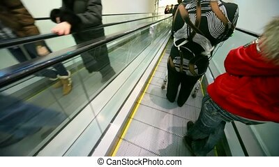 people moving on escalator, camera moving down