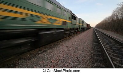 freight train formation going on rails on gravel to camera