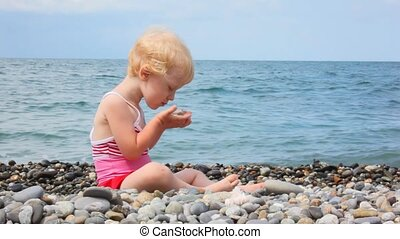 little girl sitting on pebble beach and playing with stones