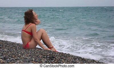 woman dressed in swimsuit sitting in pebble beach near sea