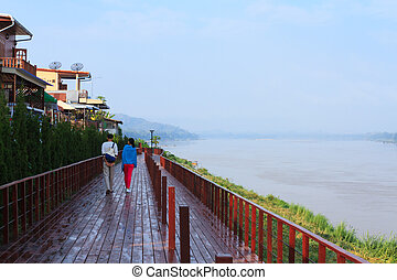 Chiang Khan Boardwalk - Two persons walk along a boardwalk...
