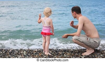 man with his little daughter throwing pebbles to sea in...