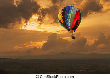 Hot air balloon over the hill at sunset