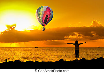 Hot air balloon over the beach with people exercise at sunset
