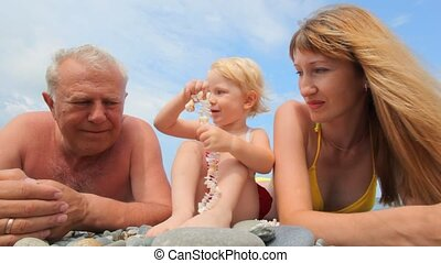 happy family of little girl, mother and grandfather lying and talking in pebble beach