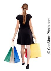 back view of going woman with shopping bags - back view of...
