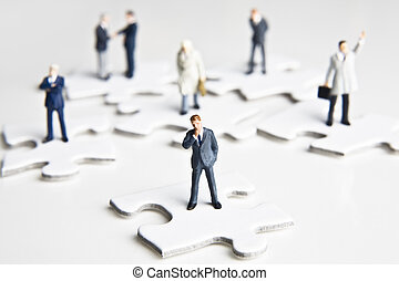 Puzzled over business - Businessmen figurines standing on...