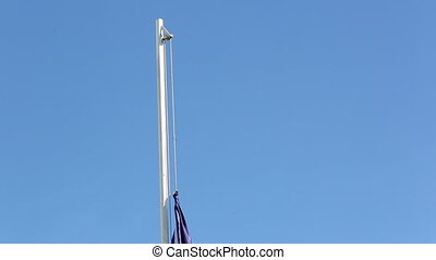 Hoist a flag of European Union in front of blue sky