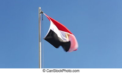 Textile flag of Egypt in front of blue sky
