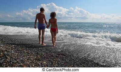 young caucasian couple has fun in sea surf, clouds in background