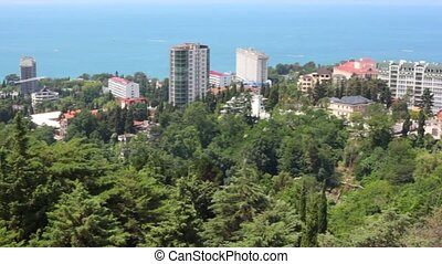 panning of resort city with sea coast and many trees, Sochi,...