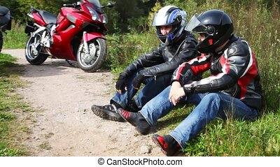 Two bikers sits near their motorcycles in park,moving camera