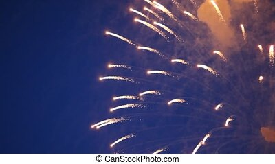 Many big multi-coloured flashes of firework in evening sky