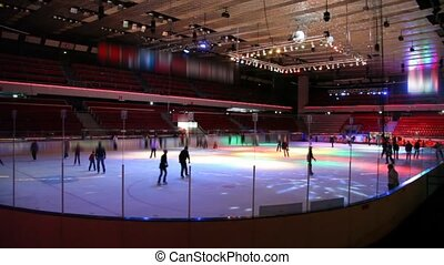 people skating on ice in roofed skating rink with illumination
