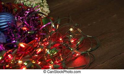 Christmas balls and garland flashing tangled on the floor