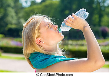 Thirsty young woman finishing water from bottle - Close up...