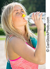 Young athlete drinking water outside - Single young blond...