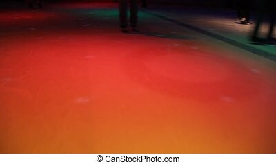 people skating in skating rink with illumination, camera...