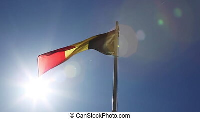 Textile flag of Belgium on a flagpole in front of blue sky