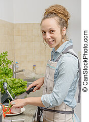 young woman in the kitchen with a tablet - a young woman in...