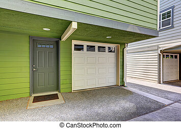 Small entrance porch and garage door of duplex house. -...
