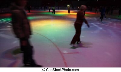 people skating in night skating rink with dynamic...
