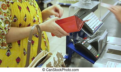 Pregnant woman gets money from her purse to calculate for goods purchased in the supermarket.