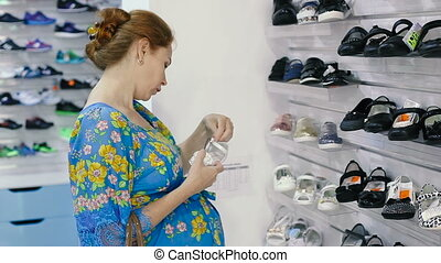 Clothes shopping in baby and maternity shop woman looking...