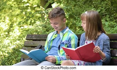 Boy and girl reading book - Teen cute boy and little girl...