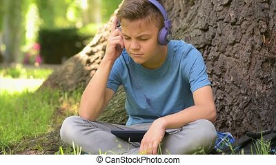 Boy with tablet at park - Teen boy 12-14 year old in...