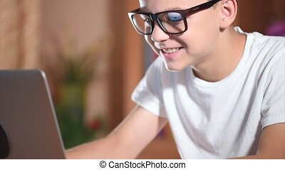 Teen boy working on laptop - Teen boy with glasses working...