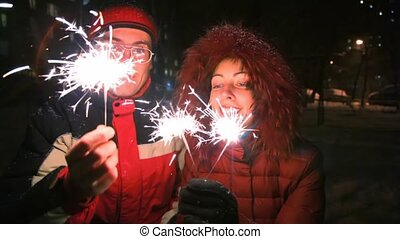 young woman and man with sparklers, night outdoor