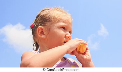 Closeup Little Girl with Pigtail Eats Fruit on Sand Beach
