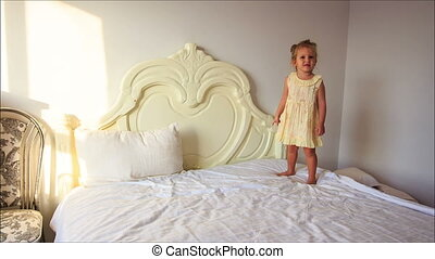 Little Girl Smiles Jumps down White Bed to Pillows on Floor