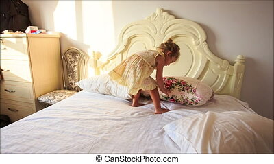 Little Girl Plays Throws down Pillows from White Bed to...