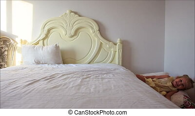 Little Girl Gambols Jumps down White Bed to Pillows on Floor...