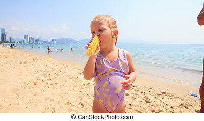 Closeup Little Girl with Pigtail Eats Fruit on Sand Beach -...