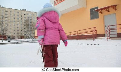 little girl carrying sled with camera on snow