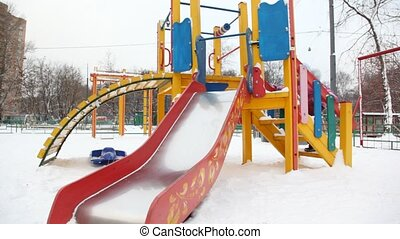 little girl playing on slide in deep snow city playground, winter