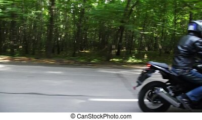 Two motorcyclists go on asphalt road. Moving camera