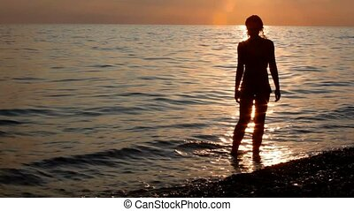 silhouette of young woman on beach, sunset sky and sea in background