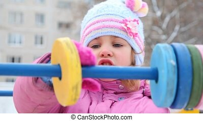 little girl playing with abacus in winter playground