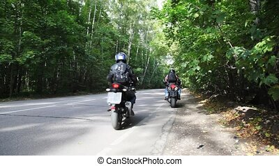 Two bikers on their bikes start on asphalt road together